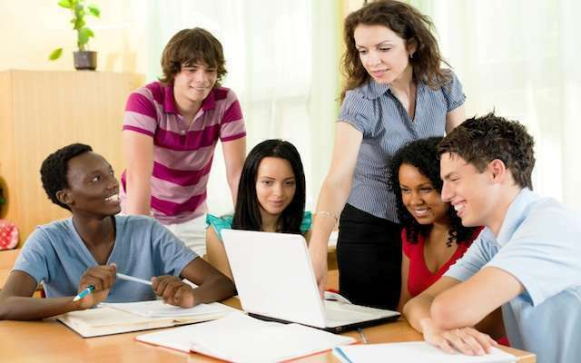 Group of teenagers and a teacher using laptop together.